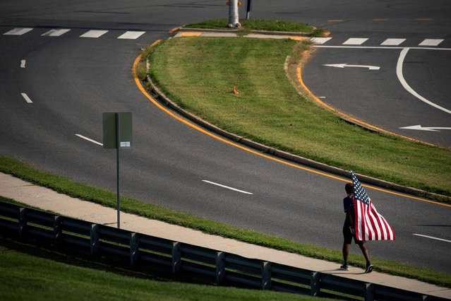 A man carries an American flag as he walks towards the Pentagon, during ceremonies commemorating the 20th anniversary of the September 11, 2001 attacks, in Arlington, Virginia, U.S., September 11, 2021. (Photo by Al Drago/Reuters)