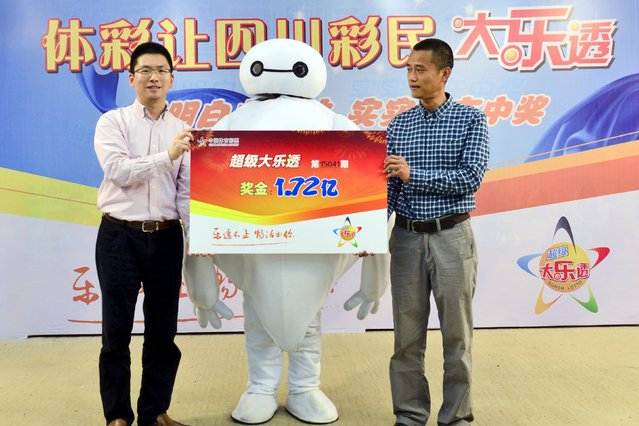 "A lottery winner (C), dressed as the inflatable robot Baymax from the Disney animated movie ""Big Hero 6"", poses with a cheque which shows his winning prize of 172 million yuan ($28 million), during a ceremony in Chengdu, Sichuan province April 16, 2015. (Photo by Reuters/Stringer)"