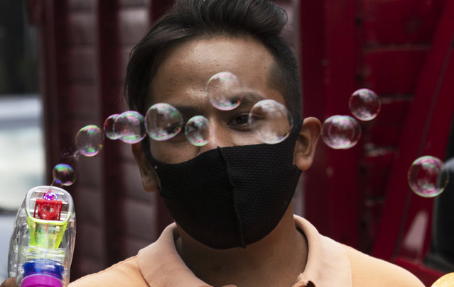Martin Santiaguillo hawks bubble toy guns along the iconic Reforma Avenue in Mexico City, Friday, August 14, 2020, amid the new coronavirus pandemic. (Photo by Marco Ugarte/AP Photo)