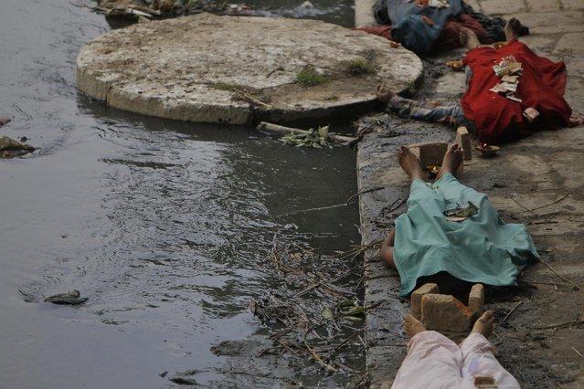 Dead bodies of earthquake victims are kept on the bank of Hanumante river for cremation in Bhaktapur near Kathmandu, Nepal, Sunday, April 26, 2015. (Photo by Niranjan Shrestha/AP Photo)