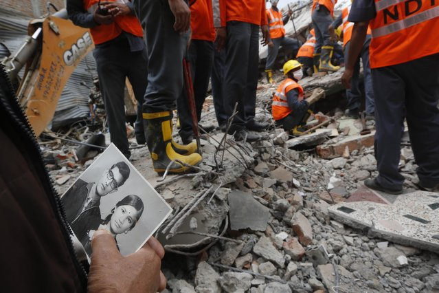 In this Tuesday, April 28, 2015 photo, a relative holds an old photograph showing Bharatman Pradhan, a 68-year-old family patriarch who survived Saturday's massive earthquake, and his deceased wife, salvaged from the debris of their collapsed house in Kathmandu, Nepal. (Photo by Manish Swarup/AP Photo)