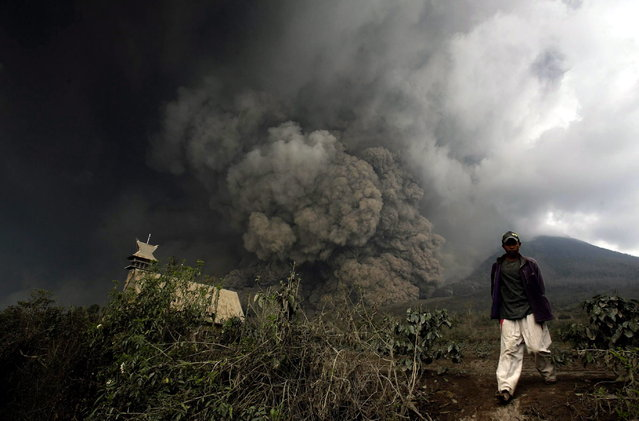An Indonesian villager flees as mounth Sinabung spews volcanic materials in Karo, North Sumatra, Indonesia, 01 February 2014. (Photo by Chairaly/EPA)