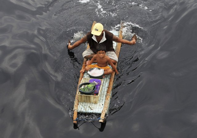 A father and his son paddle a makeshift banca made out of styrofoam and bamboo while carrying buckets full of fishes they received from local fishermen, which they plan on selling at a wet market in Navotas, metro Manila March 1, 2016. (Photo by Romeo Ranoco/Reuters)
