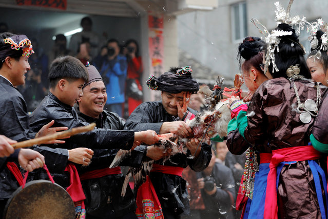 "Ethnic ""Kam"" (also known as Dong) women and men take part in a traditional wedding ritual known as the ""steal the chicken at the drum tower"". The event involves young men competing to be the first to tear apart live birds carried on poles by new brides into the village centre. (Photo by Tyrone Siu/Reuters)"