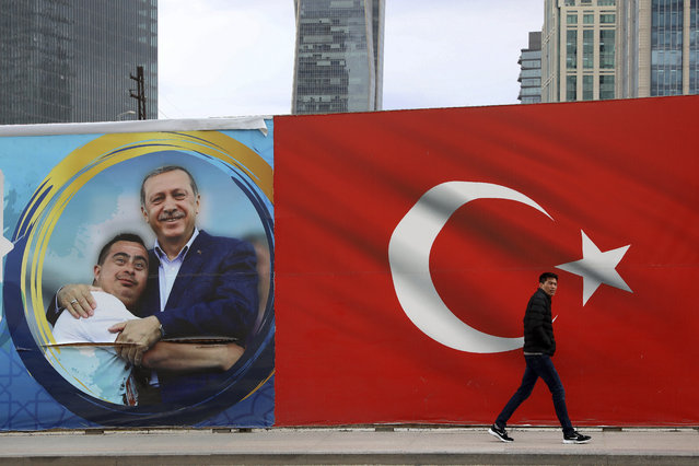 A man walks by a Turkish flag and a poster showing the Turkey's President Recep Tayyip Erdogan with a boy in Ankara, Turkey, Sunday, March 31, 2019. Turkish citizens have begun casting votes in municipal elections for mayors, local assembly representatives and neighborhood or village administrators that are seen as a barometer of Erdogan's popularity amid a sharp economic downturn. (Photo by Ali Unal/AP Photo)