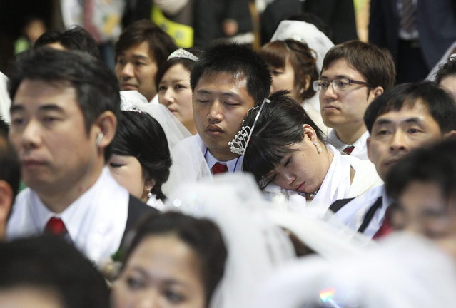 A newly-married couple takes a nap in a mass wedding ceremony at the CheongShim Peace World Center in Gapyeong, South Korea, Wednesday, February 12, 2014. (Photo by Lee Jin-man/AP Photo)
