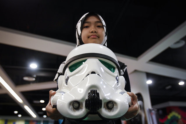 "A Malaysian Muslim girl poses with a Storm Trooper helmet at a Star Wars Day gathering in a mall downtown Kuala Lumpur, Malaysia, Saturday, May 2, 2015. Star Wars Day is observed by fans globally on May 4 with a slight change in the iconic catchphrase; from ""May the Force be with you"" to ""May the Fourth be with you"". (Photo by Joshua Paul/AP Photo)"