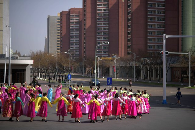"Women dance on a street as part of celebrations marking the anniversary of the birth of Kim Il Sung, known as the ""Day of the Sun"", on Mansu hill in Pyongyang on April 15, 2019. (Photo by Ed Jones/AFP Photo)"