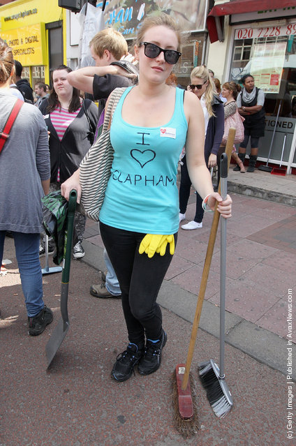 Volunteers get ready to clean up after last night's rioting at Clapham Junction on August 9, 2011 in London, England
