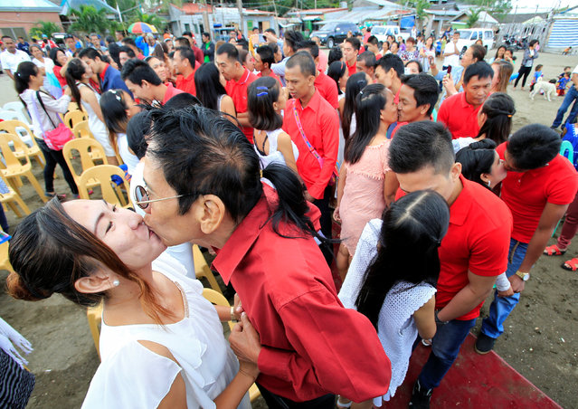 Newly-wed couples kiss during a mass wedding as part of Valentine's Day celebration in Rosario town, Cavite city, south of Manila, Philippines February 14, 2017. (Photo by Romeo Ranoco/Reuters)