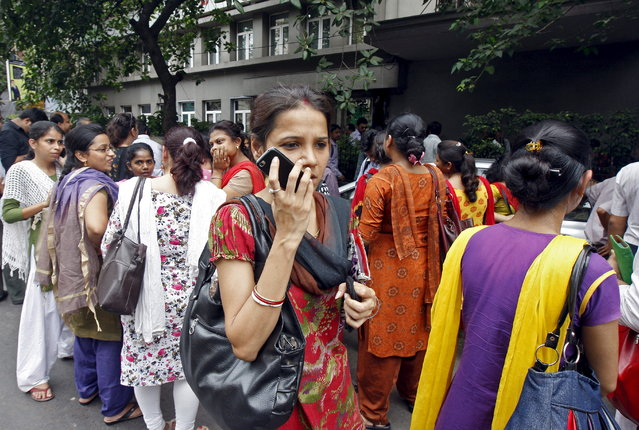 A woman speaks on her mobile phone as she stands with others after vacating their office buildings following an earthquake in Kolkata, India, May 12, 2015. (Photo by Rupak De Chowdhuri/Reuters)