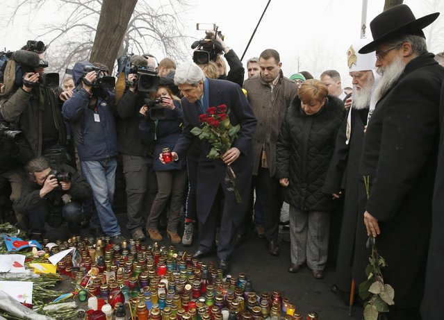 """Secretary of State John Kerry places a candle and roses atop the Shrine of the Fallen in Kiev, Ukraine, Tuesday, March 4, 2014. The Shrine of the Fallen, located on Institutska Street, honors the fallen Heroes of the """"Heavenly Sotnya"""" (Hundred). Over the course of the EuroMaidan protests, almost 100 protesters were killed by police. (Photo by Kevin Lamarque/AP Photo)"""
