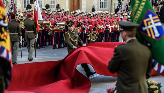 A member of the Honour Guard tries to rearrange the red capet as strong winds disturb the welcoming ceremony for Chinese President Xi Jinping (not pictured) at Prague Castle in Prague, Czech Republic, 29 March 2016. China's President Xi Jinping arrived the previous day for a two-day state visit to Prague. (Photo by Filip Singer/EPA)