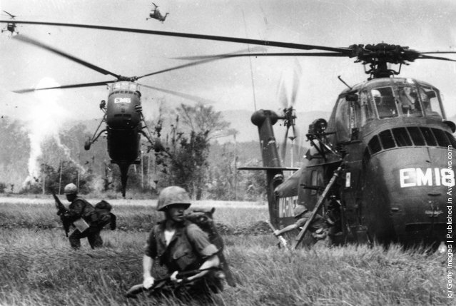 US marine troops find themselves waist-high in swampy fields, as they jump from Sikorsky S-55 helicopters