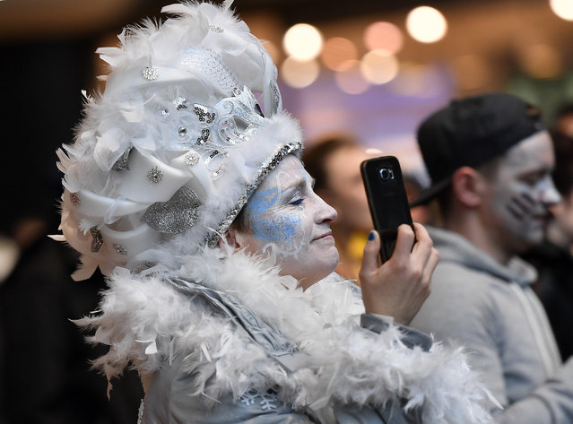 A reveler films with her phone when tens of thousands revelers dressed in carnival costumes celebrate the start of the street-carnival in Cologne, Germany, Thursday, February 23, 2017. (Photo by Martin Meissner/AP Photo)