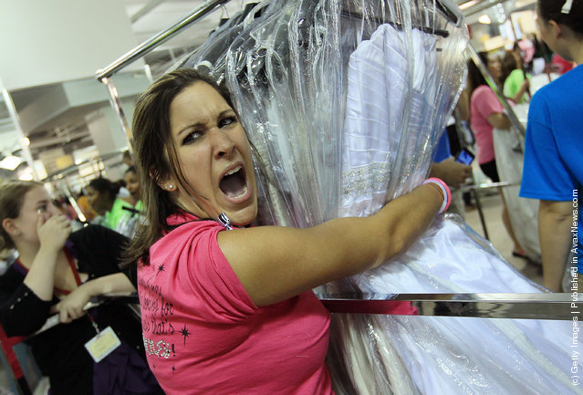 Bride to be Nicole Christos of Raleigh, North Carolina holds a rack of a wedding gowns while telling her mother that other gowns she has eyed were being taken, during Filene's Basement's annual sale