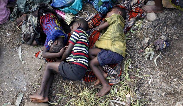 Sick Burundian refugees sleep as they wait for treatment at a makeshift clinic on the shores of Lake Tanganyika in Kagunga village in Kigoma region in western Tanzania, as they wait for MV Liemba to transport them to Kigoma township, May 17, 2015. (Photo by Thomas Mukoya/Reuters)