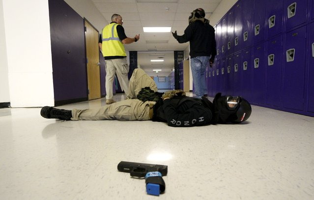 Joe Deedon (L,) president of TAC ONE Consulting, debriefs a student after a scenario with a mock victim (foreground) in a middle school during an Active Shooter Response course offered by TAC ONE in Denver April 2, 2016. (Photo by Rick Wilking/Reuters)