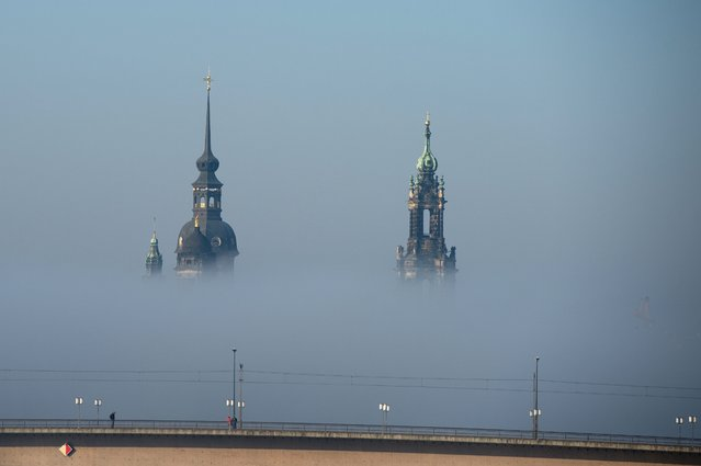The spires of the Hausmannsturm of the Schloss (L) and the Catholic Hofkirche church are visible above heavy fog in Dresden, Germany, 12 February 2015. (Photo by Arno Burgi/EPA)