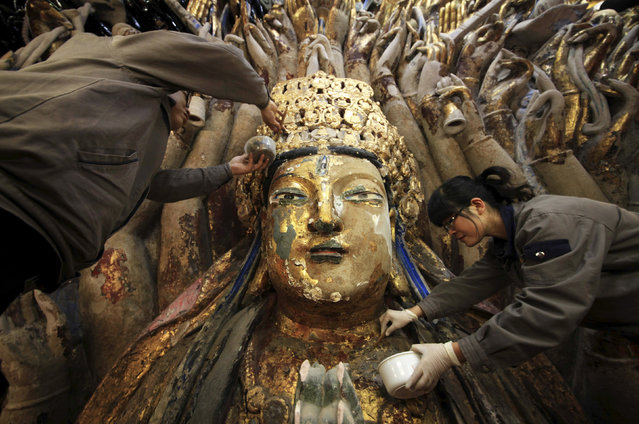 Restoration workers peel off loose gold foil as part of a restoration project for an 800-year-old Thousand-Hand Guanyin Buddhist statue on Mount Baoding in Chongqing municipality, March 18, 2014. The stone-carving statue, which takes up about 88 square metres on the mountain, dates back to the Southern Song Dynasty (1127–1279). Officials said the restoration project started in April 18, 2011 and would likely finish in the first half of 2015, local media reported. (Photo by Reuters/Stringer)