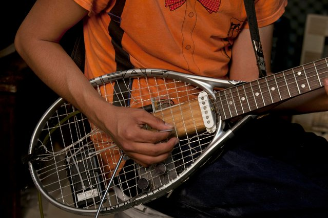 """In this Friday, April 24, 2015 photo, Fernando Lopez Ramirez plays a guitar made from a discarded tennis racquet, during a jam session in the outskirts of Mexico City. Lopez Ramirez and his brothers, cousins and friends are members of the """"Orquesta Basura"""" or Trash Ochestra. They collect trash items like pots, pans, wooden boxes, hub caps and tennis racquets from the trash in their neighboorhood and turn them into musical instruments. (Photo by Marco Ugarte/AP Photo)"""