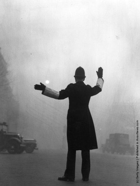 A policeman on traffic duty on a foggy day in Fleet Street, London, 1952