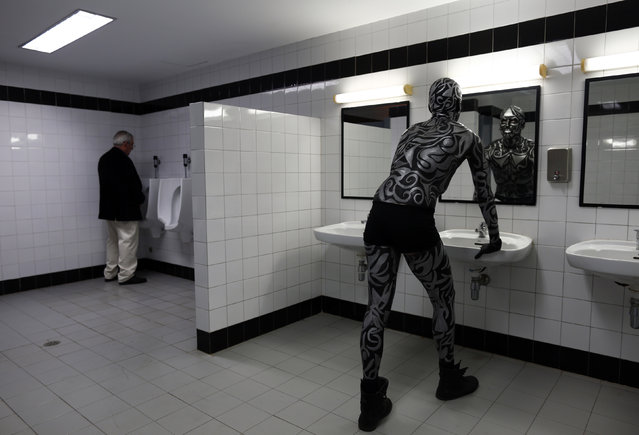 Ruben Hidalgo, 25, a contestant, looks at his reflection in the mirror at a bathroom before taking part in a body paint pageant during Expobelleza Andalucia (Expobeauty Andalusia) in the Andalusian capital of Seville March 24, 2014. (Photo by Marcelo del Pozo/Reuters)