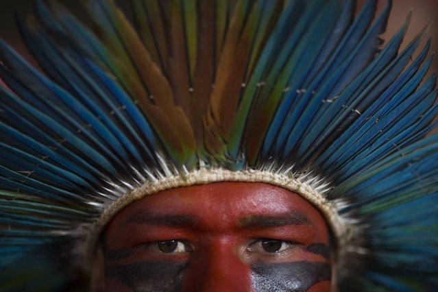 An indigenous man listens to speeches during a rally of Social Movements for Democracy, in a camp set up by supporters of President Dilma Rousseff in Brasilia, Brazil, Saturday, April 16, 2016. The lower chamber of Brazil's Congress on Friday began a debate on whether to impeach Rousseff, a question that underscores deep polarization in Latin America's largest country and most powerful economy. The crucial vote is slated for Sunday. (Photo by Felipe Dana/AP Photo)