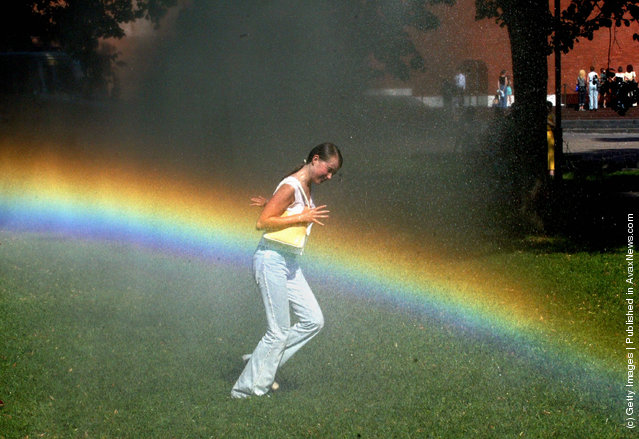 A girl runs through a water sprinkler escaping the heat in Alexandrovski Garden July 15, 2002 in Moscow, Russia