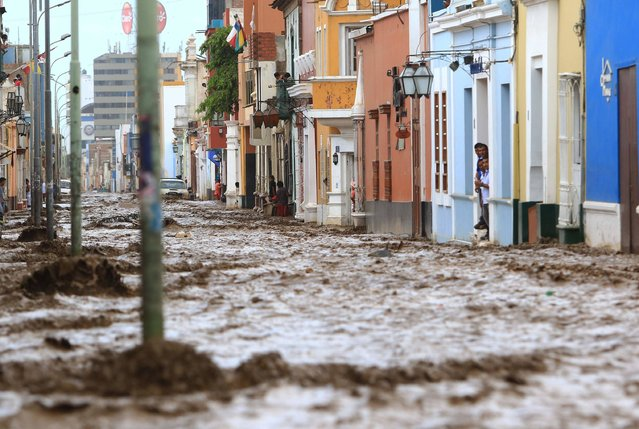 A flash flood hits the colorful historic centre of the city of Trujillo, 570 kilometres north of Lima on March 18, 2017, bringing mud and debris. The El Nino climate phenomenon is causing muddy rivers to overflow along the entire Peruvian coast, isolating communities and neighbourhoods. Thousands have been affected since January, and 72 people have died. Most cities face water shortages as water lines have been compromised by mud and debris. (Photo by Celso Roldan/AFP Photo)