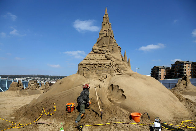 "A sand sculptor works on the final touches of a sand sculpture being built as part of this year's ""Once Upon a Time"" themed annual Weston-super-Mare Sand Sculpture festival on April 16, 2014 in Weston-Super-Mare, England. (Photo by Matt Cardy/Getty Images)"
