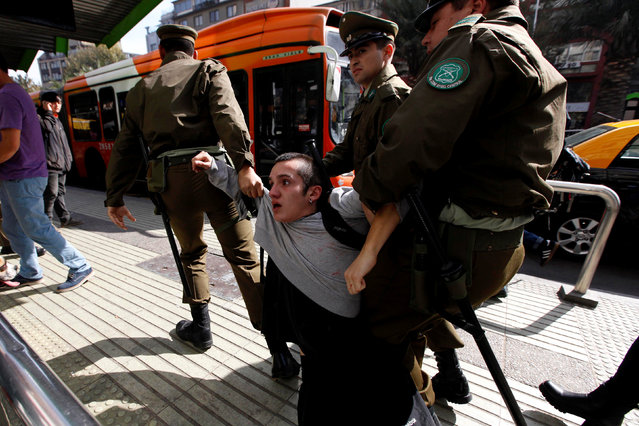 A demonstrator is detained during a rally in support of an identity check draft law and against delinquency, in Santiago, Chile April 30, 2016. (Photo by Carlos Vera/Reuters)