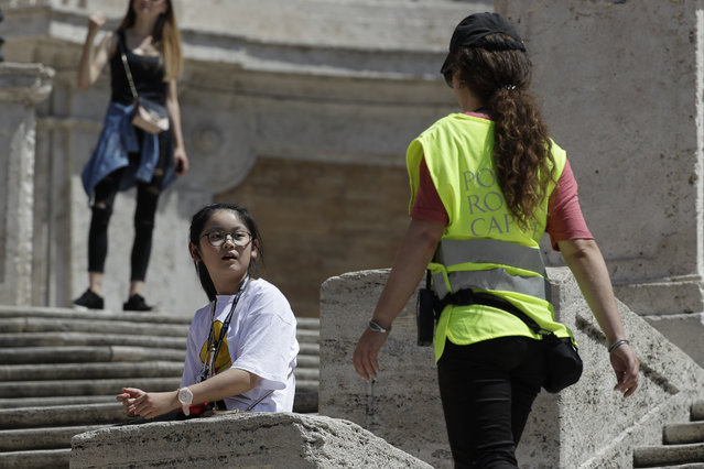 A Police officer asks a girl not to sit on the Spanish Steps, in Rome, Wednesday, August 7, 2019. Police started the enforcement of a law designed to protect monuments and landmarks and are forbidding people from sitting on the Spanish steps since they are considered a monument. (Photo by Gregorio Borgia/AP Photo)