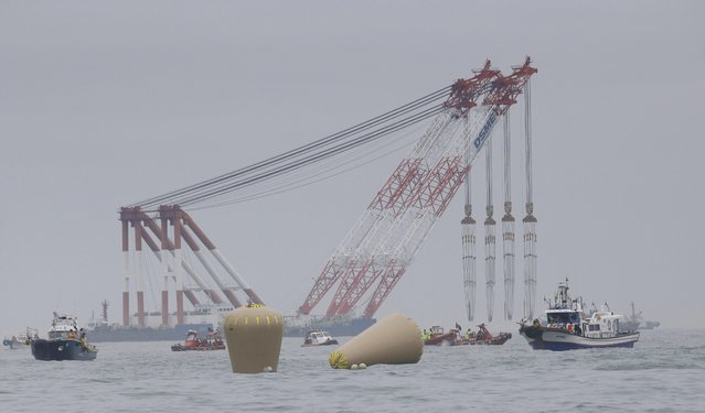 Cranes wait near the buoys installed to mark the sunken 6,852-ton ferry Sewol in the water off the southern coast near Jindo, south of Seoul, South Korea, Friday, April 18, 2014. Rescuers scrambled to find hundreds of ferry passengers still missing Friday and feared dead, as fresh questions emerged about whether quicker action by the captain of the doomed ship could have saved lives. (Photo by Lee Jin-man/AP Photo)