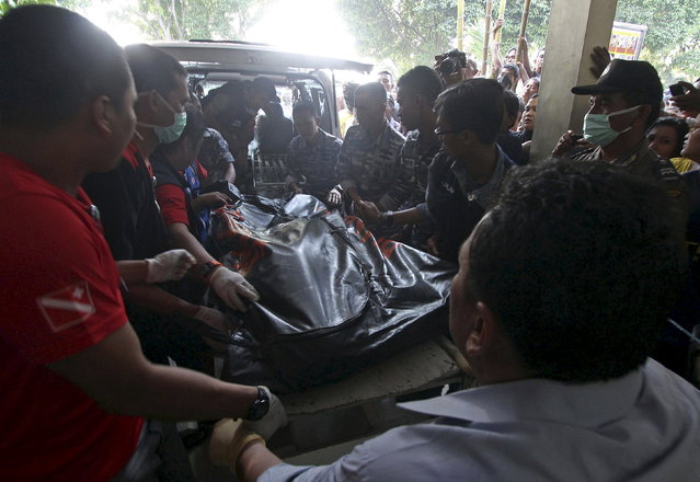 The body of a victim from an Indonesian military C-130 Hercules transport plane that crashed into a residential area, arrives at Adam Malik hospital in the North Sumatra city of Medan, Indonesia, June 30, 2015. (Photo by Septianda Perdana/Reuters/Antara Foto)