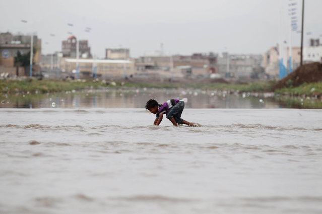 A yemeni boy wades through a flooded street after heavy rains in Sana'a, Yemen, 26 July 2019. As Yemen enters the rainy season from July to September, the United Nations says there are fears of a spread of cholera, a waterborne disease which is endemic in the country. (Photo by Yahya Arhab/EPA/EFE)