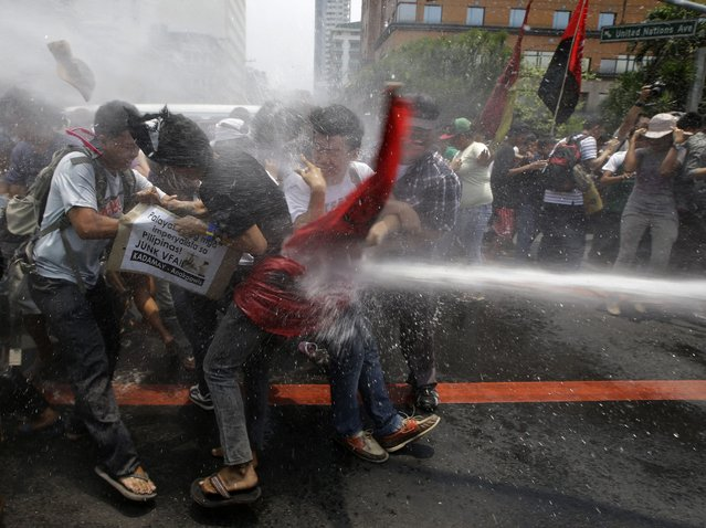 Police train their fire hose at protesters as the latter try to force their way closer to the U.S. Embassy for a rally against next week's visit of U.S. President Barack Obama Wednesday, April 23, 2014 in Manila, Philippines. Philippine police armed with truncheon, shields and water hose have clashed with more than 100 left-wing activists who rallied at the U.S. Embassy in Manila to oppose a visit by Obama and a looming pact that will increase the American military presence in the Philippines. (Photo by Bullit Marquez/AP Photo)