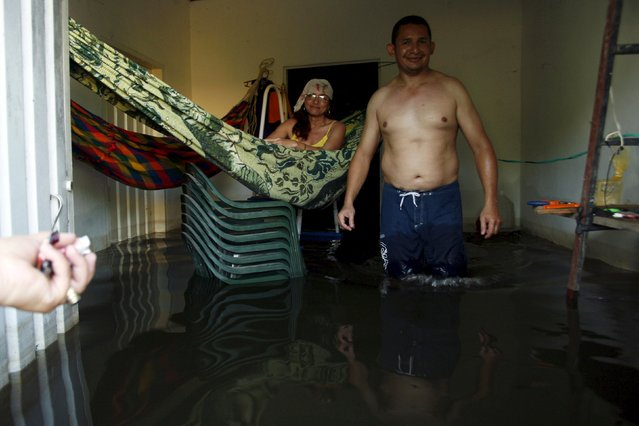 People are seen in to a flooded house in Guasdualito, in the state of Apure, Venezuela, July 4, 2015. (Photo by Carlos Eduardo Ramirez/Reuters)