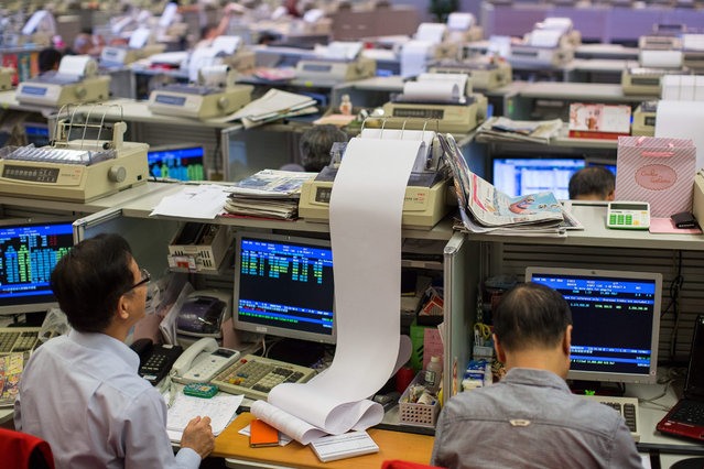 Stockbrokers work in front of a screen displaying share prices at the Hong Kong Exchanges and Clearing Limited in Hong Kong, China, 08 July 2015. Hong Kong stocks closed at a 6-month low as jitters from the mainland market spilled over across the border. (Photo by Jerome Favre/EPA)