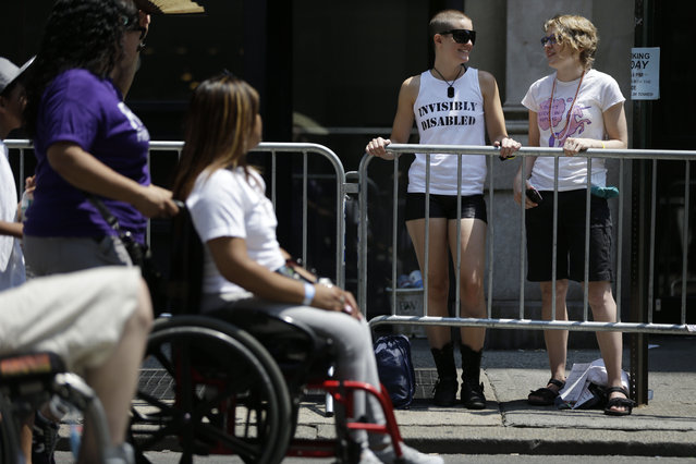 Emily Brooks, right, and Molly Marx, second from right, watch the inaugural Disability Pride Parade, Sunday, July 12, 2015, in New York. (Photo by Seth Wenig/AP Photo)