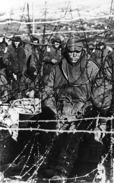 A dejected Argentinian prisoner sits behind barbed wire in a compound on the Falklands Islands during the war with British forces, June 1982. Over 1200 ARgentinians were captured at Goose Green and Darwin