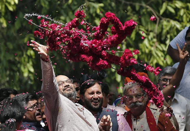 Amit Shah, a leader of BJP, throws a garland toward supporters during celebrations after learning of poll results outside the party headquarters in New Delhi, on May 16, 2014. Opposition candidate Narendra Modi will be the next prime minister of India, with early election results showing the pro-business Hindu nationalist and his party headed for the biggest victory the country has seen in 30 years. (Photo by Adnan Abidi/Reuters)