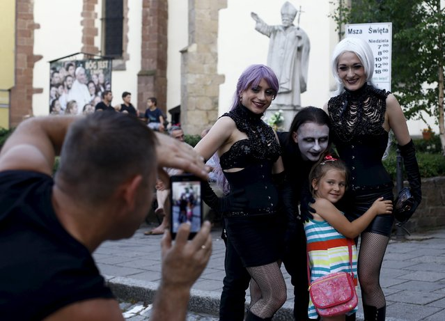 A man takes picture of young girl posing with participants of the Castle Party in front of the church in Bolkow, southwestern Poland, July 17, 2015. The annual festival features around 50 musicians and artists playing on various stage Gothic rock and other styles of the dark music subculture. Outside Germany, it is one of the biggest festival with this genre of music, the event attracts regular international audience of up to 5000, the organizers said. (Photo by Kacper Pempel/Reuters)