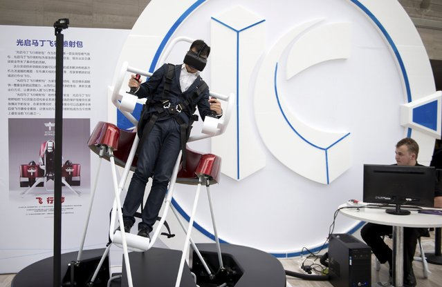 A man tests a simulator of the flying jetpack made by Martin Aircraft, at a innovation exhibition in Shenzhen, Guangdong province, China, July 20, 2015. The jetpack made its debut appearance in China on Monday in the southern city of Shenzhen, at a unit price of 1.6 million yuan ($260,000 USD), local media reported. (Photo by Reuters/Stringer)