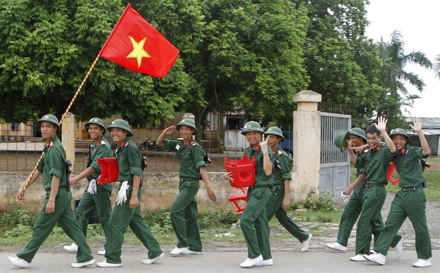 Soldiers salute as they return from training session at a military base in Hoa Lac, outside Hanoi July 24, 2015, for an upcoming military parade to mark the 70th anniversary of Vietnam's National Day on September 2. (Photo by Reuters/Kham)
