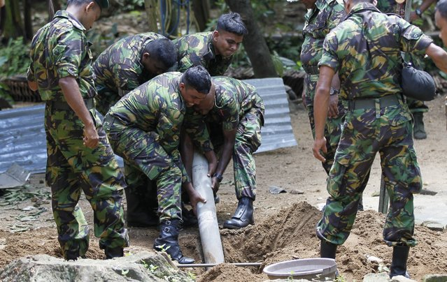 Sri Lankan police commandos dig out an artillery shell which landed in a backyard of a house after a fire at a military base in Salawa, about 35 kilometres (22 miles) east of Colombo, Sri Lanka, Monday, June 6, 2016. Minister of Law and Order Sagala Ratnayake said the fire started at a small arms depot and then spread to other depots where heavy weapons, such as artillery shells, were stored. (Photo by Eranga Jayawardena/AP Photo)
