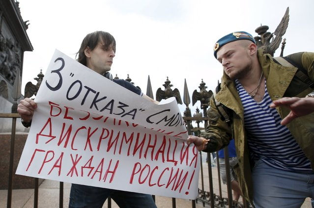 "A man (R) celebrating Paratroopers Day attempts to take away the placard of a gay rights activist who is taking part in a protest in Dvortsovaya Square in St. Petersburg, Russia, August 2, 2015. The holiday for the Russian airborne troops has been annually celebrated since the Soviet era till today. The placard reads ""Three refusals from Smolny is lawlessness and discrimination against the citizens of Russia!"". (Photo by Maxim Zmeyev/Reuters)"