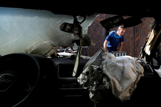 A Palestinian man inspects a vehicle that was set on fire in the southern Nablus, in the Israeli-occupied West Bank on November 22, 2019. (Photo by Mohamad Torokman/Reuters)