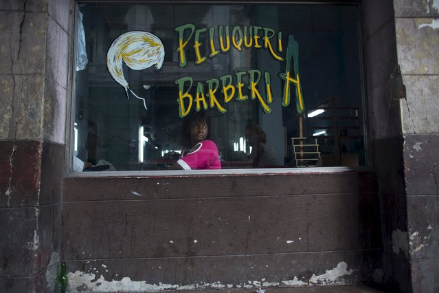 A woman who did not want to give her name, sits at the window of a barber shop in downtown Havana, April 16, 2015. (Photo by Alexandre Meneghini/Reuters)