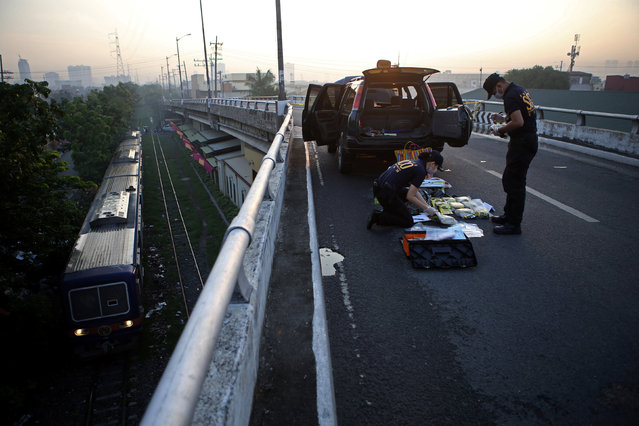 Philippine National Police Scene of the Crime Operations officers inspect 10 kilograms of methamphetamine, known as Shabu, worth around 50 million pesos, found in an abandoned vehicle on a bridge in metro Manila, Philippines June 2, 2016. (Photo by Romeo Ranoco/Reuters)